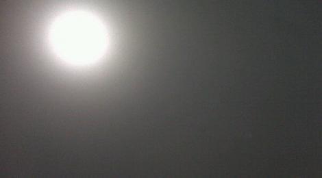 The sun was like a pale spot in the darkened sky