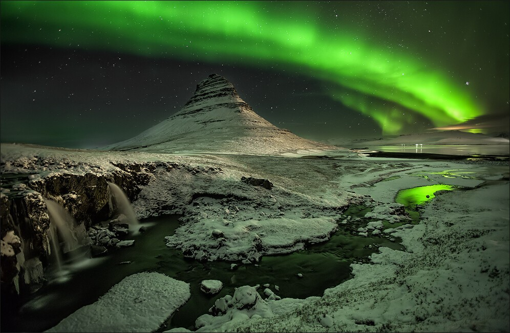 Kirkjufell with the northern lights dancing in the winter sky.