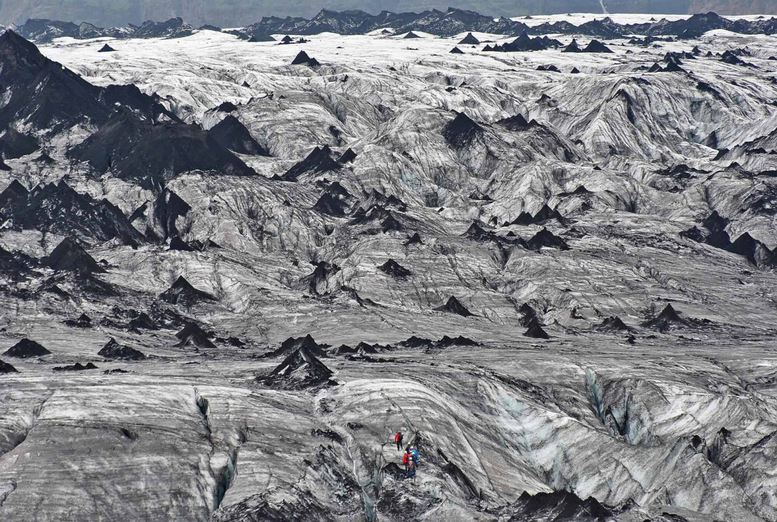 My most favourite shot! Hikers climbing the glacier peaks of Sólheimajökull in South Iceland. By the eruption of the Eyjafjalla in 2010 the glacier is contaminated with ash that the ice shades in all kinds of varies grey and even black colors.