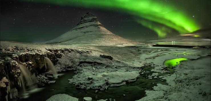 Kirkjufell with the northern lights in Iceland dancing in the winter sky. Photo by Martin Schulz.