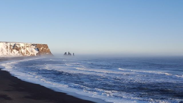 The view of Reynisfjara Black Beach from Dyrholaey promontory in Iceland.