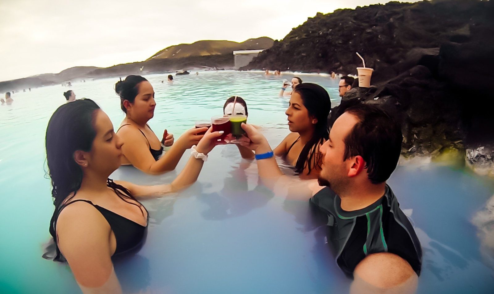 Four people having a drink in the Blue Lagoon in Iceland in winter.