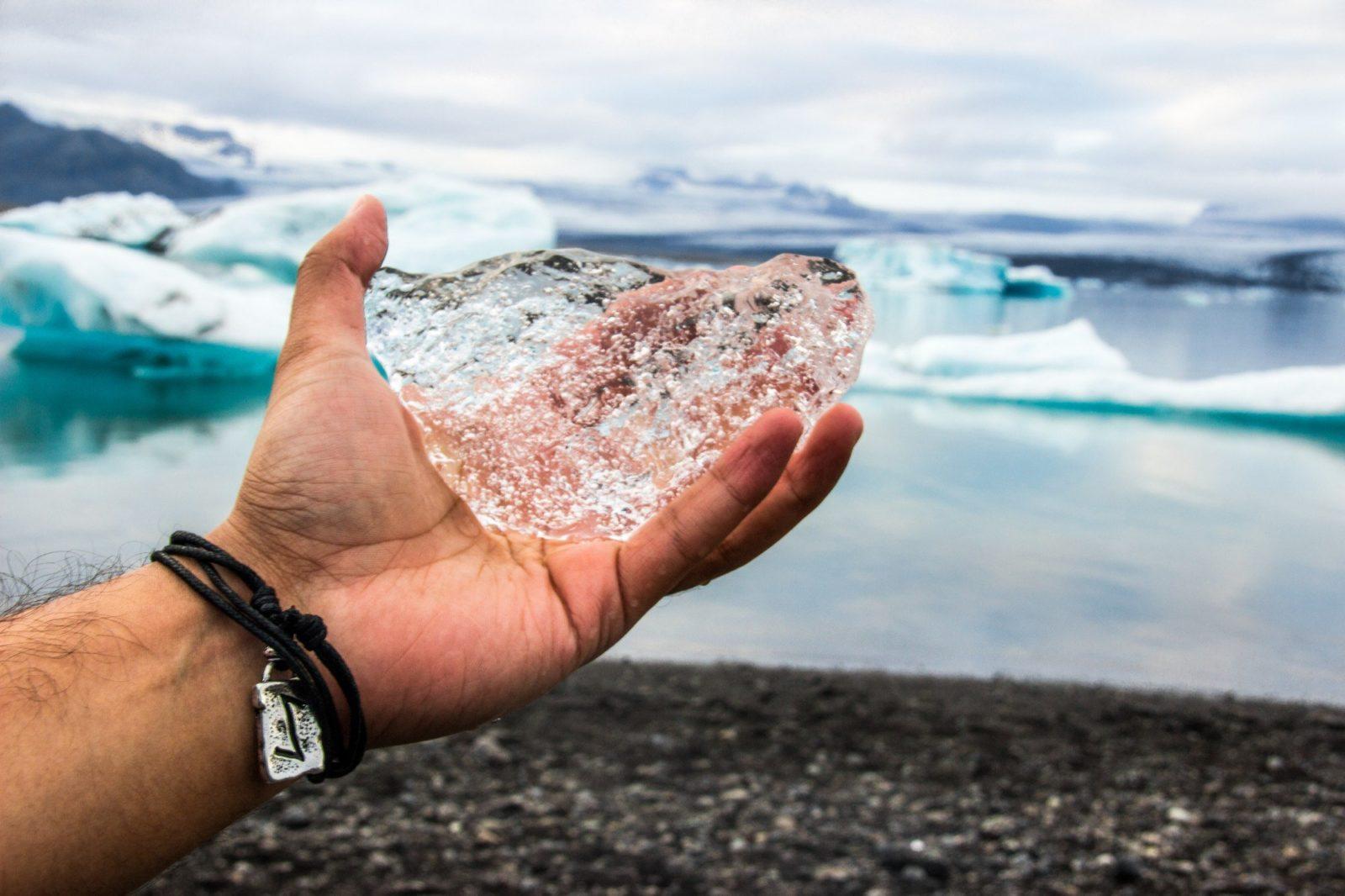 Hand with a piece of ice at the Breidamerkursandur beach in Icelandþ